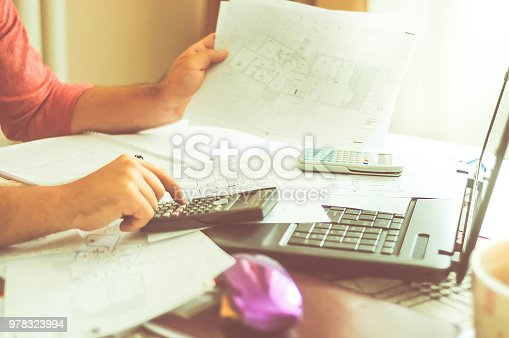 638881988istockphoto Close up of engineers hands working on table, he drawing project sketch in construction site or office 978323994