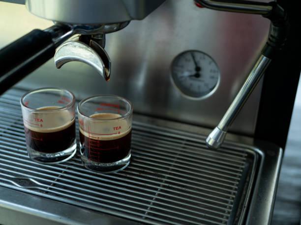 close up of espresso machine making coffee in restaurant - argento metallo caffettiera foto e immagini stock