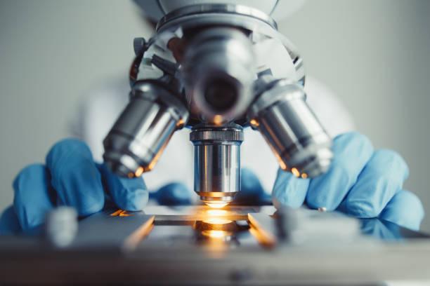 zbliżenie badania próbki badanej pod mikroskopem - laboratorium zdjęcia i obrazy z banku zdjęć