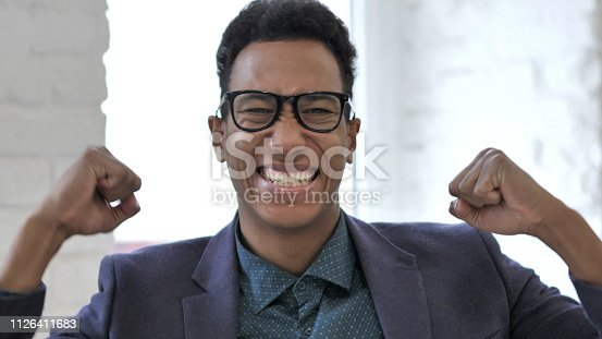 888751614 istock photo Close Up of Excited African Man Celebrating Success 1126411683