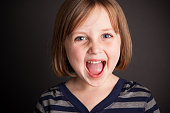 Close up, color image of an excited, ecstatic six-year-old girl, with black background.
