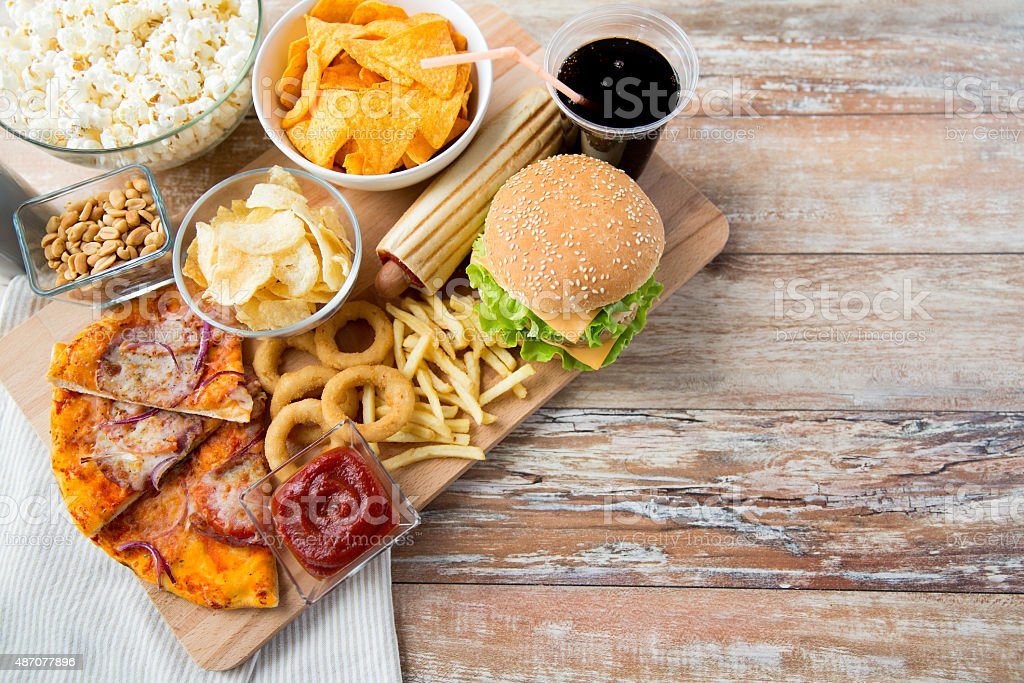 close up of fast food snacks and drink on table stock photo