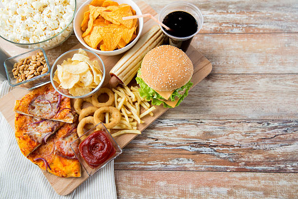 close up of fast food snacks and drink on table - snack stockfoto's en -beelden