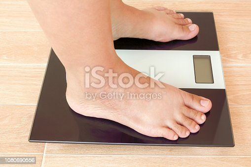 istock Close up of fat female feet standing on weight scale. 1080690556