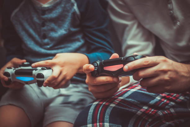 Close up of father and son playing video game.