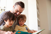 Close Up Of Father And Sons Reading Story At Home