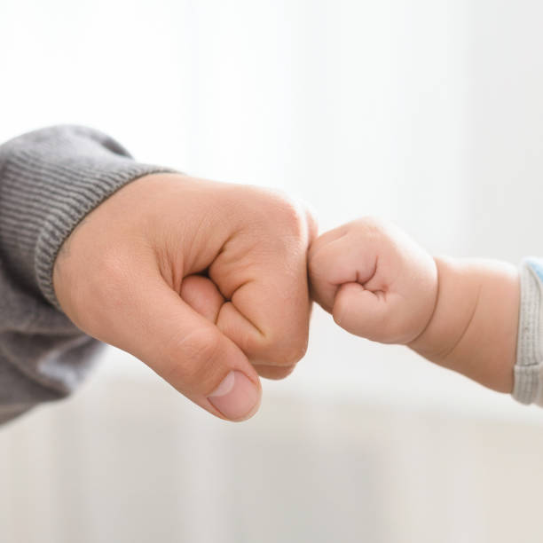 close up of father holding baby hand - bumpy stock pictures, royalty-free photos & images