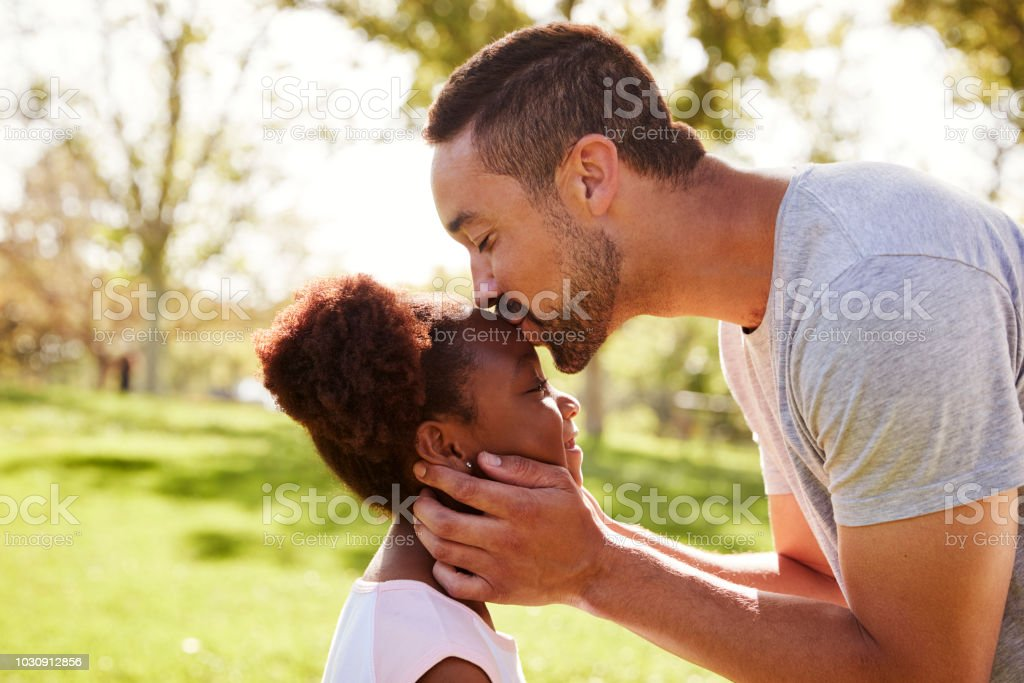 Close Up Of Father Kissing Daughter In Park Close Up Of Father Kissing Daughter In Park 30-39 Years Stock Photo