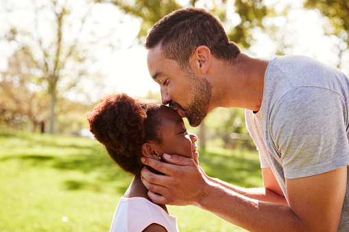 Close Up Of Father Kissing Daughter In Park Stock Photo - Download Image Now