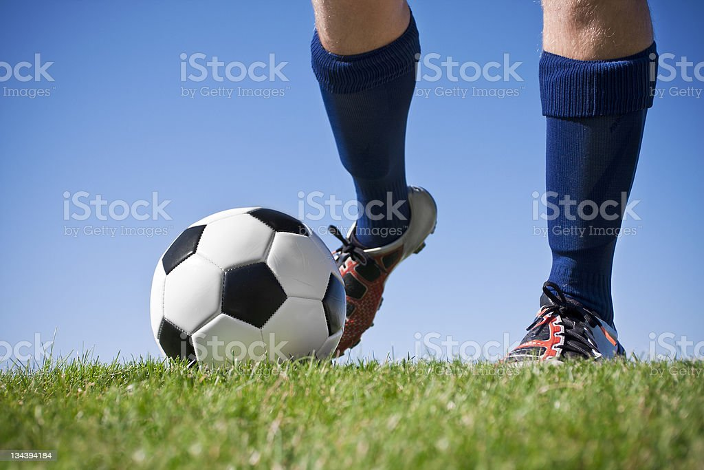 Close up of feet in blue socks kicking a soccer ball stock photo