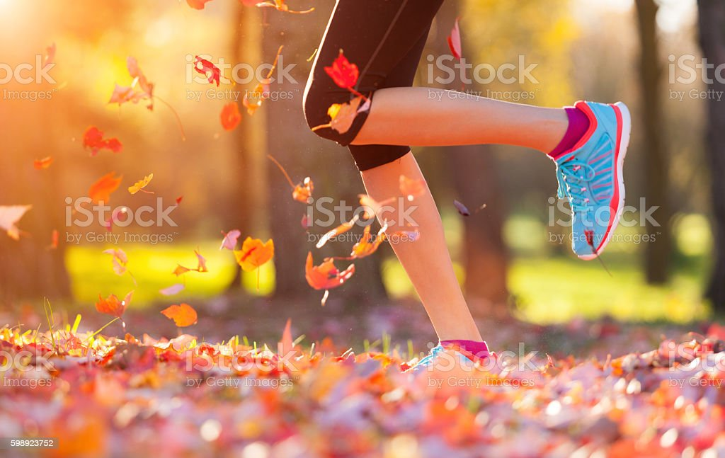 Close up of feet of a runner running in leaves stock photo