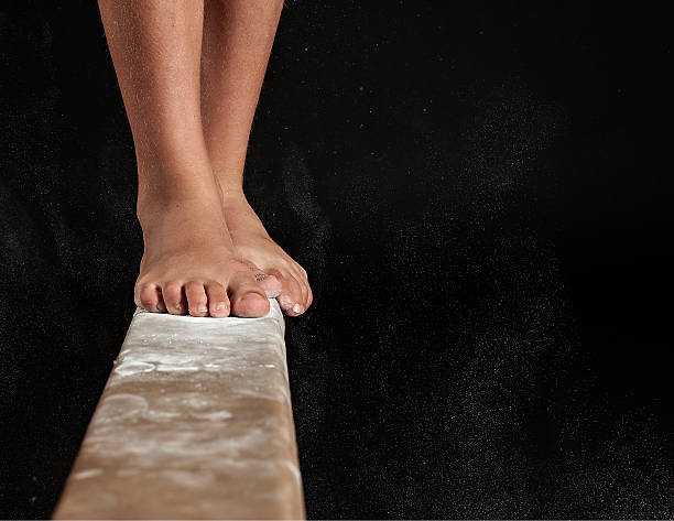 close up of feet on balance beam - balance beam stock photos and pictures