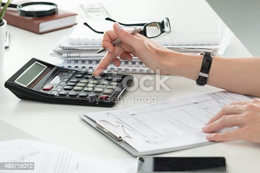istock Close up of female accountant or banker making calculations 493715012