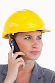 istock Close up of female architect on her cellphone with helmet on 824956110