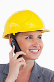 istock Close up of female architect with cellphone and helmet on 824956128