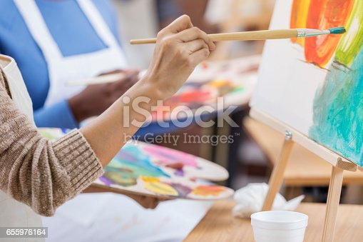 Unrecognizable woman works on a painting. She is using a paintbrush as she paints on a canvas. She is holding a palette. People are painting in the background.