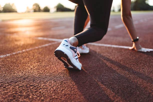 nahaufnahme der athletin, die sich darauf vorbereitet, auf der strecke zu laufen. fokus auf sneakers - joggerin stock-fotos und bilder