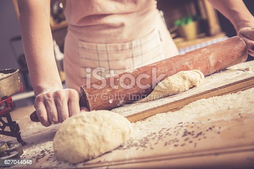 istock Close up of female baker hands kneading dough. 627044048