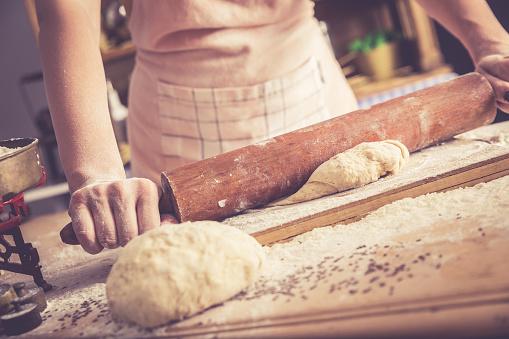 Close up of female baker hands kneading dough.