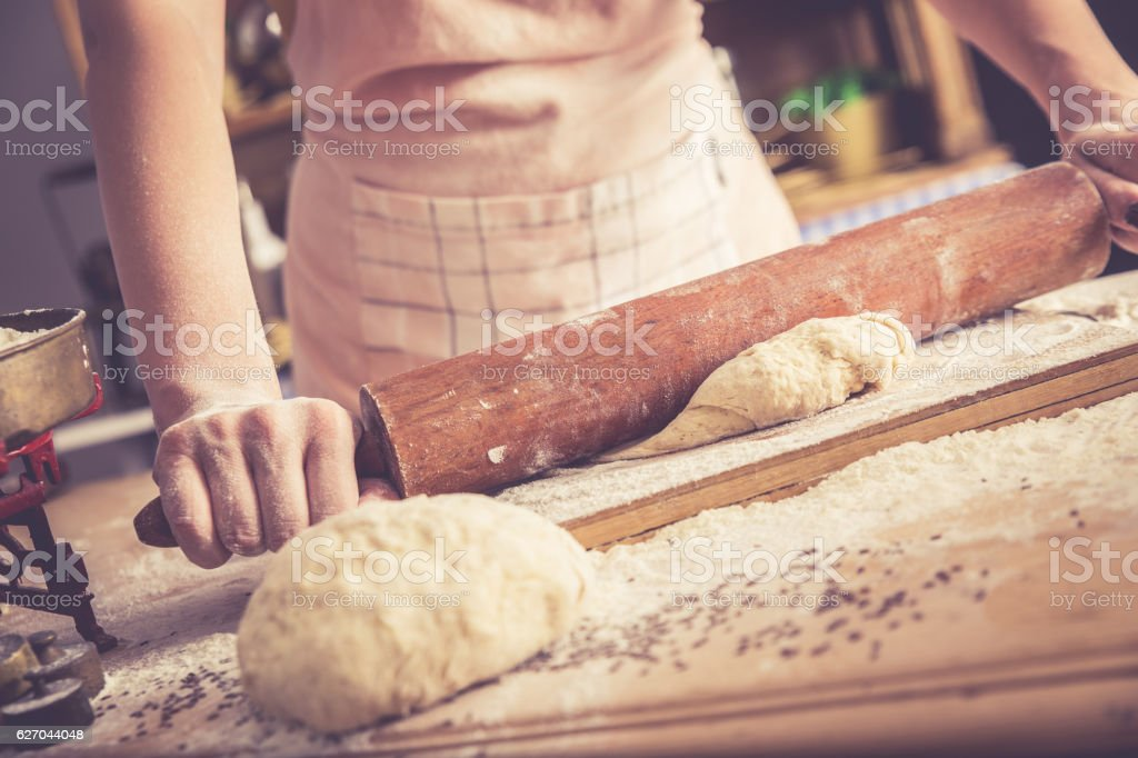 Close up of female baker hands kneading dough. stock photo