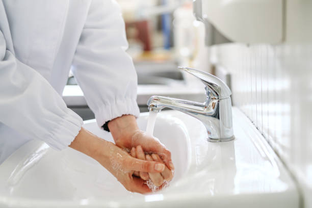 Close up of female employee washing hands in sink before working in food factory. Close up of female employee washing hands in sink before working in food factory. infectious disease stock pictures, royalty-free photos & images