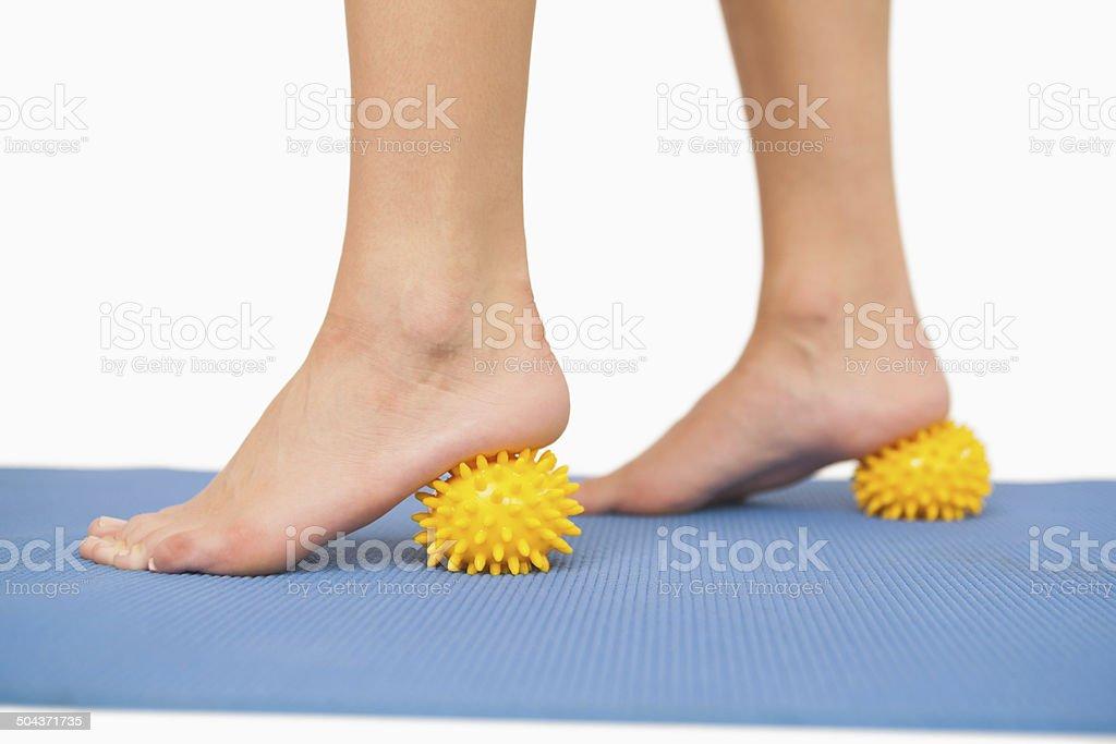 Close up of female feet touching massage ball stock photo