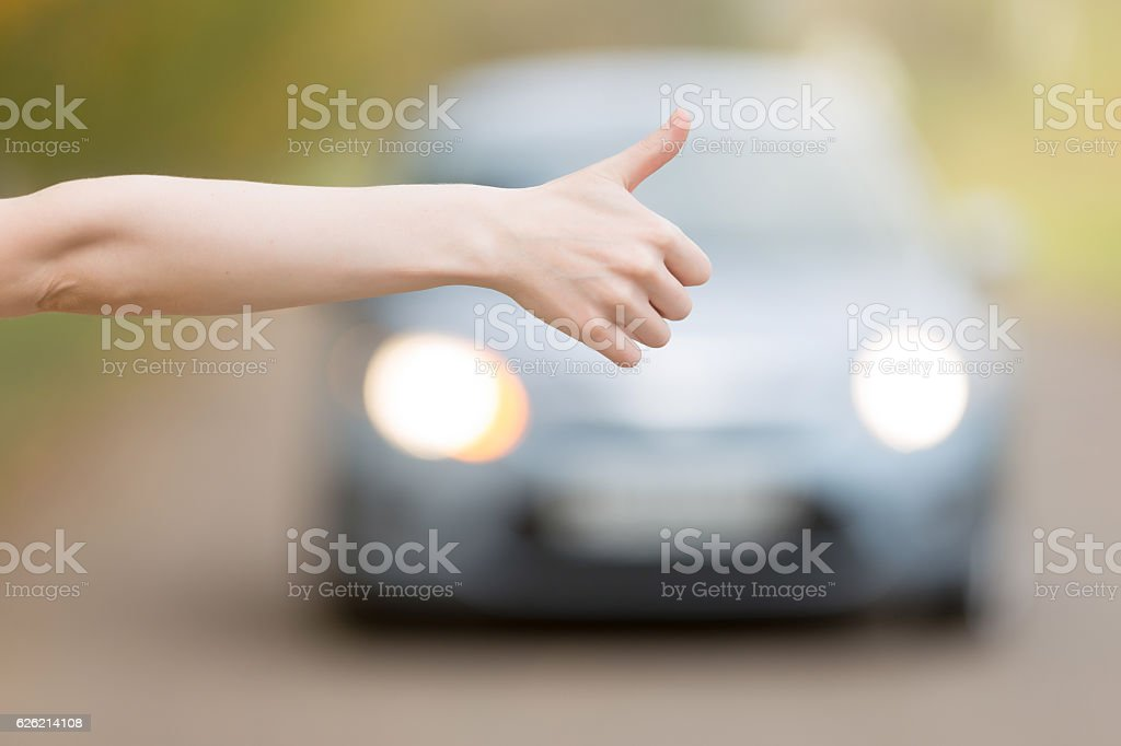 Close up of female hand hitchhiking stock photo