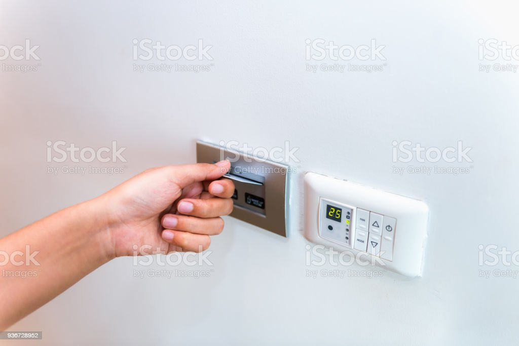 Close up of female hand inserting key card to unlock a door in the hotel stock photo