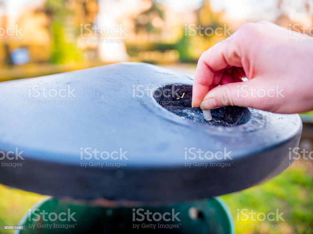 Close-up da mão feminina que põe para fora um cigarro no cinzeiro do parque ao ar livre - foto de acervo