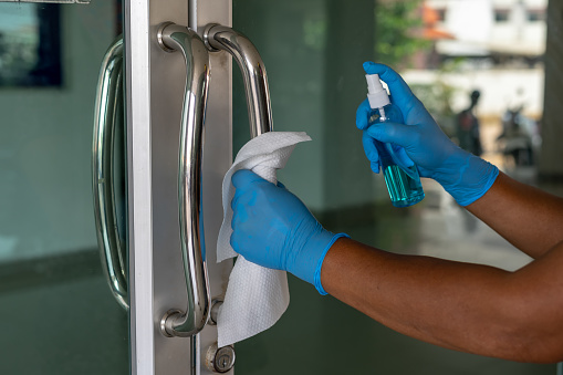 Close up of female hand using wet wipe and hand sanitizer spray to clean the door handle before touch and open the door.Antiseptic,disinfection ,cleanliness and heathcare, anti virus concept. anti Corona virus (COVID-19).