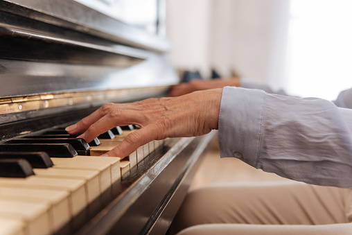 Close up of female hand while playing the piano