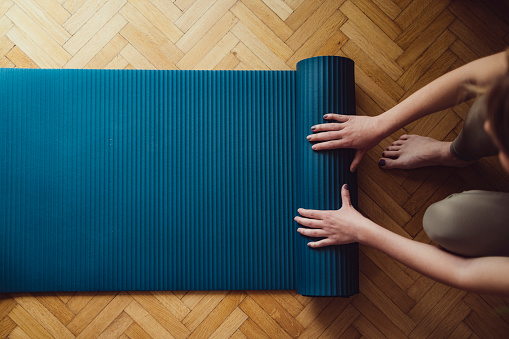 Top view of woman folding fitness mat before or after working out at home
