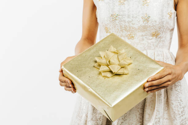 close up of female hands holding a golden gift with bow - carlos david stock pictures, royalty-free photos & images