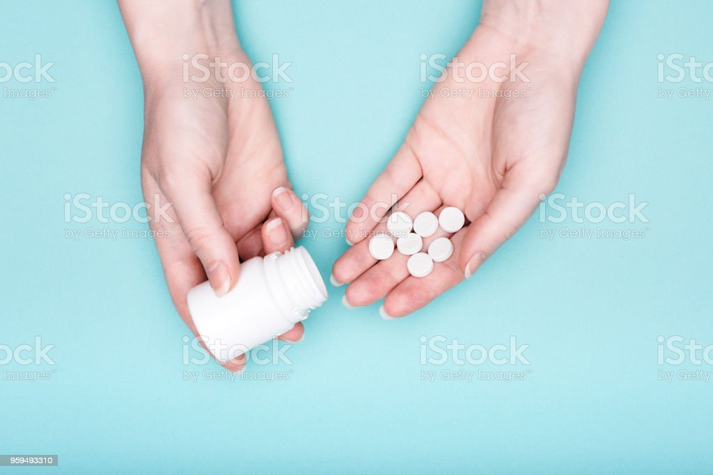 Close up of female hands holding medication bottle and white pills over pastel blue background. Patient taking medication. stock photo