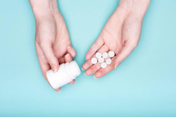 nahaufnahme von weiblichen händen mit medikation flasche und weißen pillen über pastell blau hinterlegt. patienten-einnahme von medikamenten. - schmerzmittel stock-fotos und bilder