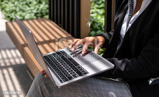 Unrecognizable business woman sitting on bench, working on laptop computer outside