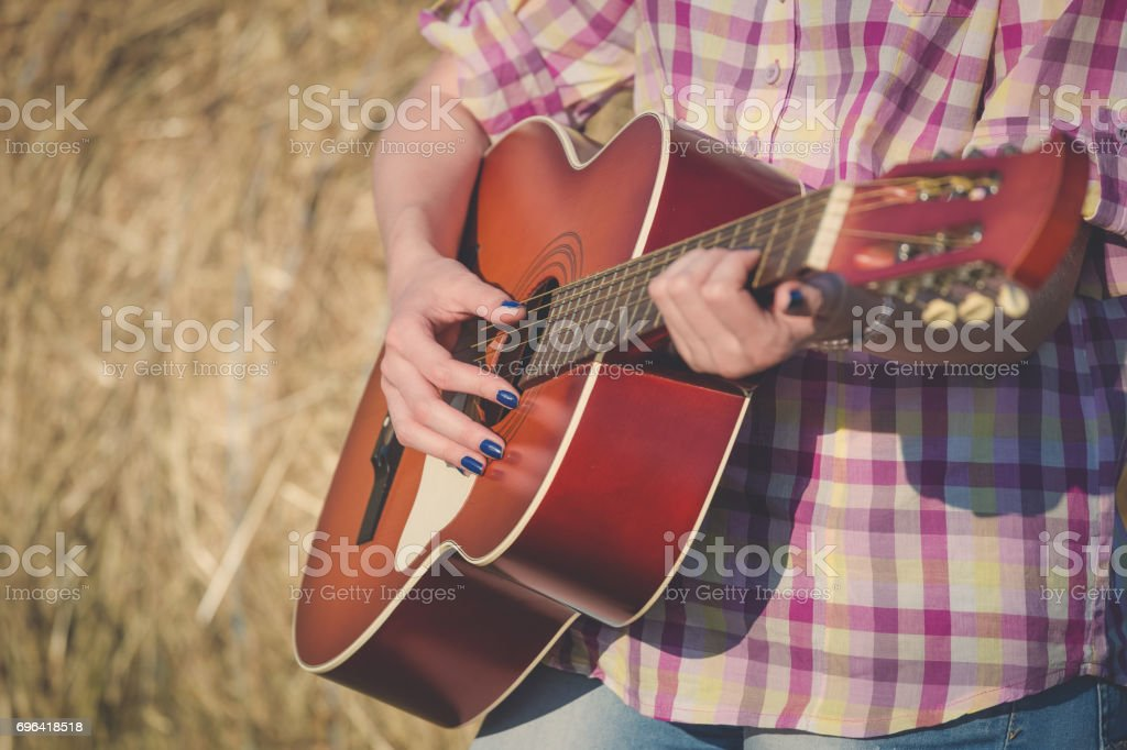 Close up of female hands playing acoustic guitar outdoors. Retro, music and lifestyle concepts. stock photo