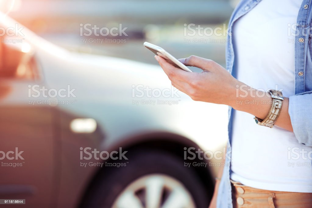 Close up of female hands texting SMS next to the car. stock photo