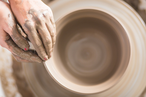 Close up of female hands working on potters wheel