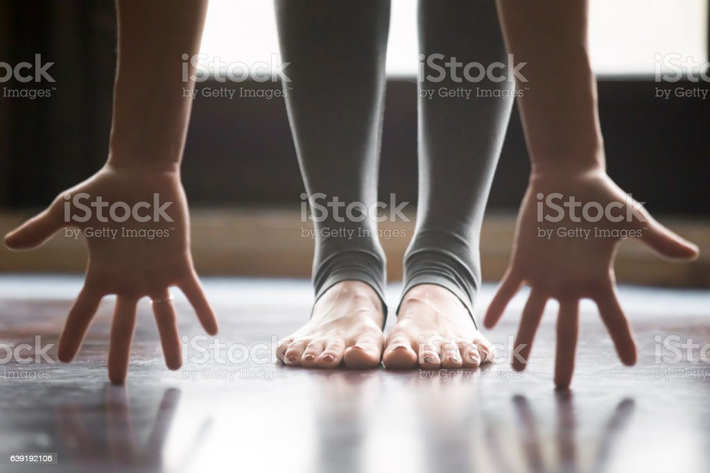Close up of female in uttanasana pose, legs yoga pants stock photo