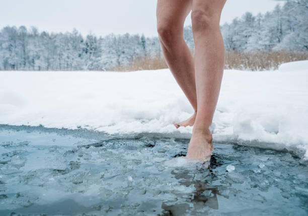Close up of female legs getting into ice cold water stock photo