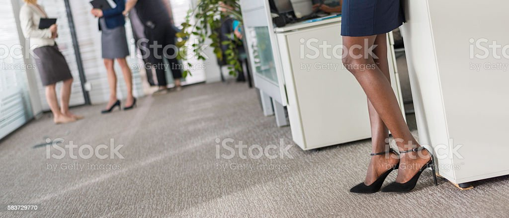 Close up shot of a woman\'s legs wearing high heels, people in...