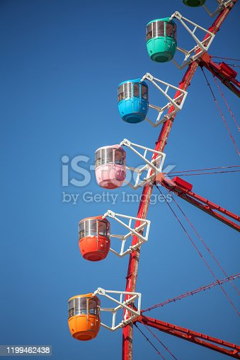 Close up of ferris wheel in front of blue sky, vertical