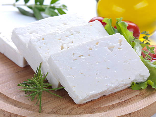 """close up of feta slices """"feta cheese cut in slices, vegetables, herbs and olive oil-the ingredients for a greek salad"""" feta cheese stock pictures, royalty-free photos & images"""