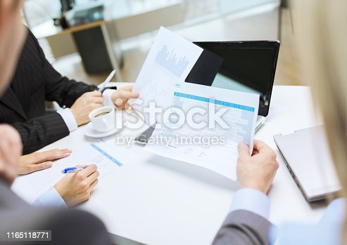 business and office concept - close up of business team with files and laptop computer in office