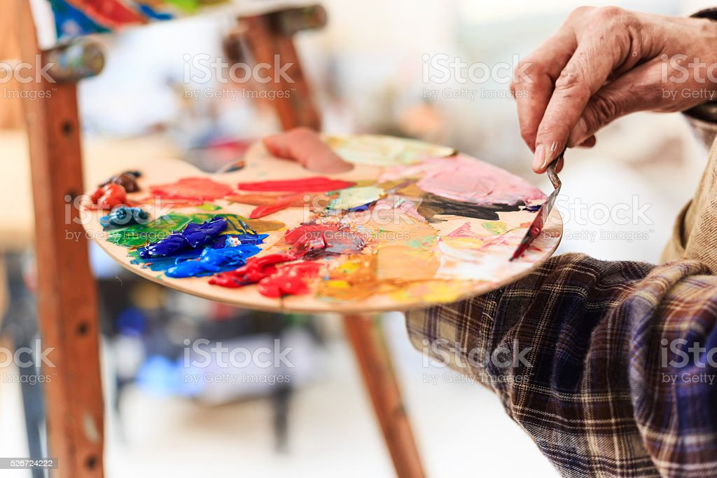 Close up of fine art painter's hand working at workshop stock photo