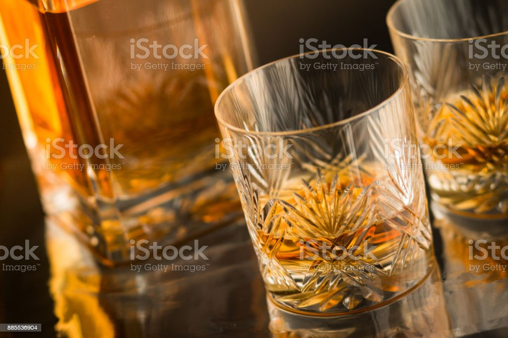 Close up of fine crystal tumblers with malt Scotch whisky on reflective bar counter with decanter in background stock photo
