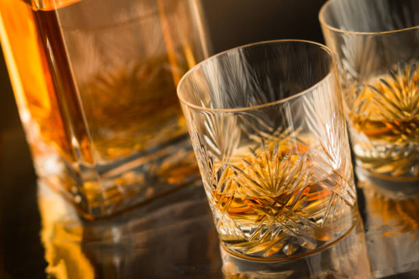 close up of fine crystal tumblers with malt scotch whisky on reflective bar counter with decanter in background - crystal glassware stock photos and pictures