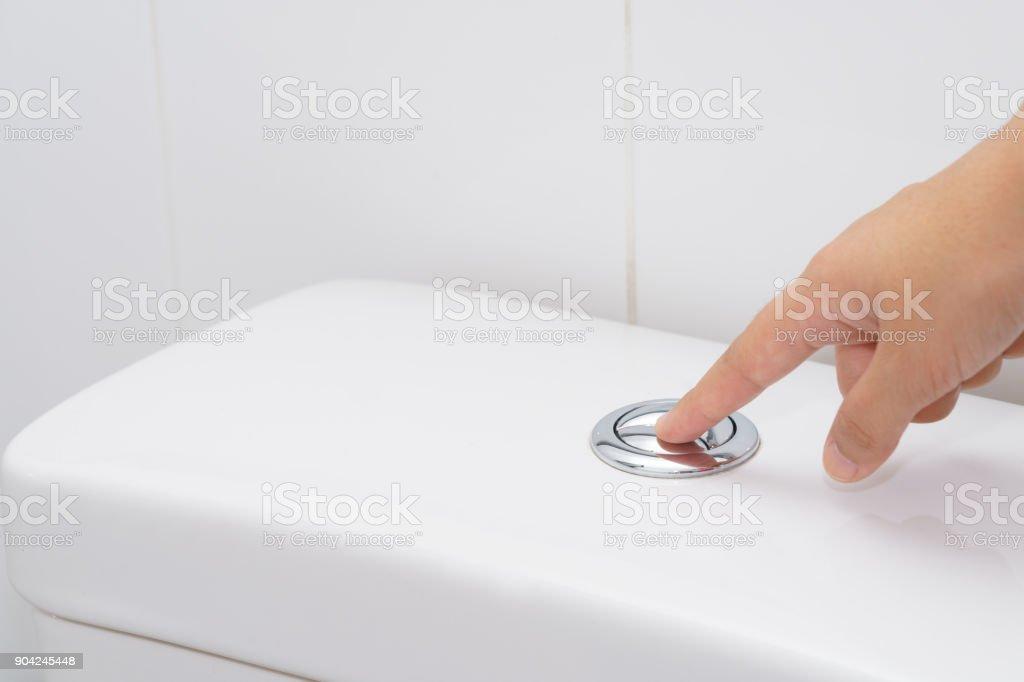 Cerca del dedo presionando un botón del inodoro con descarga para la limpieza. -ahorrar agua concepto - foto de stock