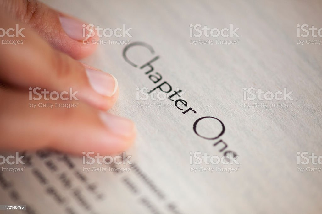 Close up of fingers on chapter one of book stock photo